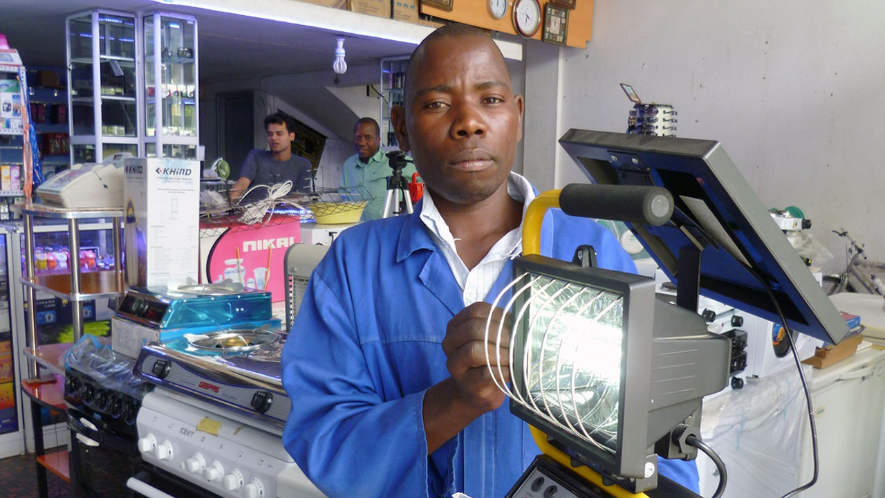 A workshop technician displaying a solar powered lamp